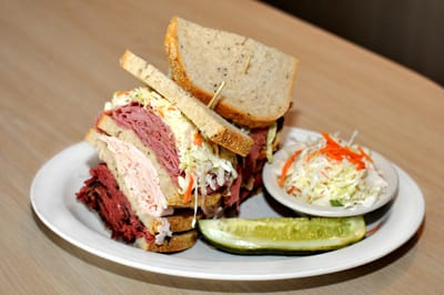 Dig into a made-to-order sandwich bursting with hot pastrami, turkey, hot corned beef, and cole slaw on deli rye Sherman's Deli & Bakery.