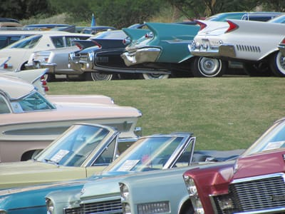 A cluster of classic cars, including a 1968 Chrysler 2300 (yellow), a '68 Impala, '68 Cadillac,'59 DeSoto , '60 Cadillac Fleetwood, and a pink and white 1958 Edsel.