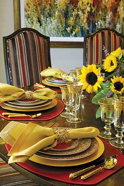Plates: Philippe Deshoulieres Limoge Dhara porcelain. Flatware: Ricci Leopardo Gold. Goblets: Arte Italica. Chargers: gold leaf lacquerware. Napkin rings: L'Objet. Placemats: Sybaritic in red Italian vinyl. Napery: gold on gold linen with silk border. Courtesy Tuverson & Co., Palm Desert.
