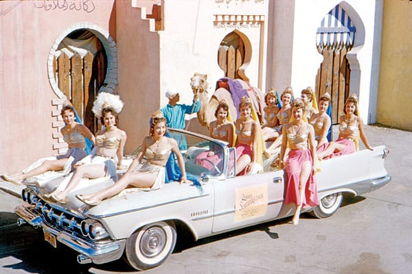"""""""A turban- and tunic-clad man with camel at hand stands beside a dozen desert beauties in pseudo-Arabian cheesecake dress, posing on a Space Age-style 1959 Imperial Convertible. Welcome to Americana!"""""""