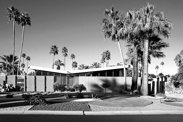 "In this first Palm Springs subdivision by the George Alexander Construction Co., these practical well-designed homes have worked perfectly over six decades. Each is the same footprint, with few variations. In a neighborhood appearing to be custom homes, each house represented a new ideal: a 1,600-square-foot example of innovative, efficient ""merchant housing"" — tract houses, but architectural. The Parking, Breezeway, Windows, Wall pattern started here. Some included tiny open-air atriums aside a tinier but distinct master bedroom foyer, bringing day-lit gardens inside. Clerestory windows framing treetops and mountains provide lighting but also privacy and wall space for furniture and art. Butterfly, vaulted, and flat rooflines over wood, rock, stucco, brick, and decorative concrete block mingle in a fusion of natural and manufactured materials. Front landscaping was included in the purchase price (architect William Krisel also was the landscape architect), but you were on your own in back — although a 20-foot-by-40-foot swimming pool was included."