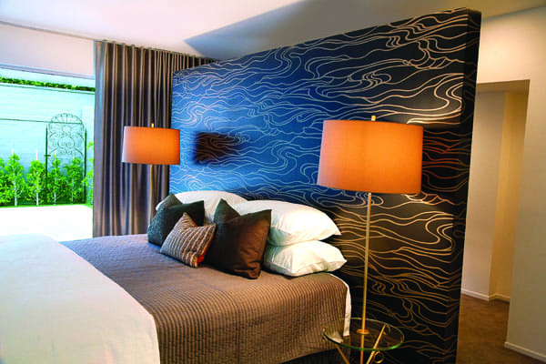 A freestanding wall covered in wallpaper serves as an oversized headboard in the master bedroom. Behind it are closets.