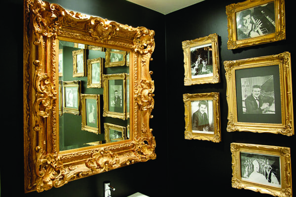 An ornately framed mirror and photographs of Liberace in the powder room evoke the spirit of the flamboyant showman.