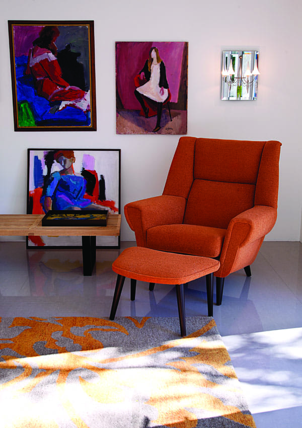 The David Chair from the Christopher Kennedy Collection, upholstered in Michael Jon Marvelous Melon, sits before The Plume Sconce by Baccarat and paintings by MaryAnn Gladfelter, a late relative of the homeowners. (A matching chair and sconce are outside the frame of this image.)