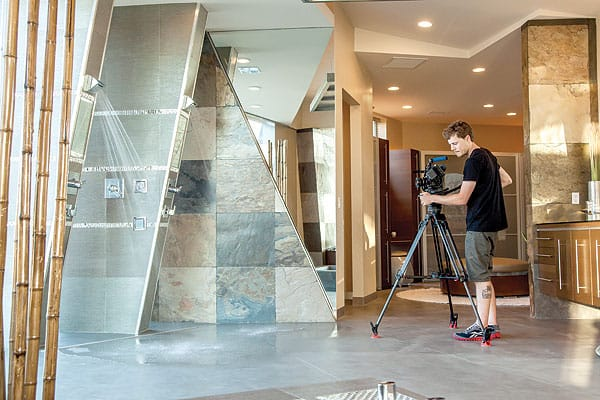 "Foster spent $100,000 for glass and fittings, another $100,000 on the structural span shower ""pods,"" and more than $100,000 on the tub, which is surrounded by a pool of water that continues to an infinity edge on the other side of a glass wall."