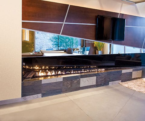 Mirroring the rest of the suite, the fireplace wall combines multiple materials. Brian Foster told <em>Million Dollar Rooms</em> host Carter Oosterhouse he wanted to create an environment that had something of an industrial look, but also felt comfortable enough for casual living.