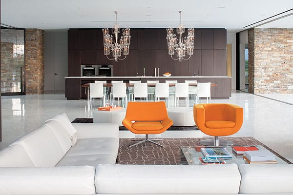 The main living space — which encompasses a kitchen, dining area, and living room centered around a massive stone fireplace — reinforces the open, midcentury modern-style design sensibilities of the house. Sleek furnishings reinforce the minimalist aesthetic while providing ample and comfortable accommodations for family and guests.