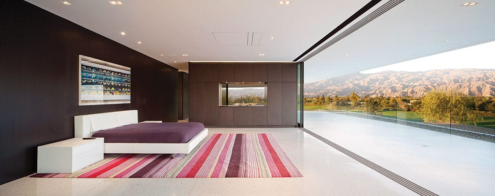 Floor-to-ceiling glass doors slide open with ease and disappear into wall pockets. Outside, overhangs protect the interior from the sun, while taking advantage of the natural light and breezes.