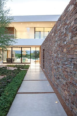 The walls extend from the entry courtyard through the entire length of the house, protecting the interior from winds out of the north and extreme heat from the south.
