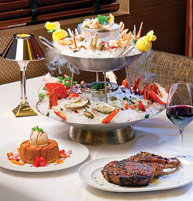Mastro's Steakhouse: Clockwise from bottom: 33-ounce Chef's Cut Bone-in Rib-Eye Chop; Warm Butter Cake with ice cream, oranges, berries, and whipped cream; and the dramatic Smoking Three-Tier Iced Seafood Tower appetizer for sharing.