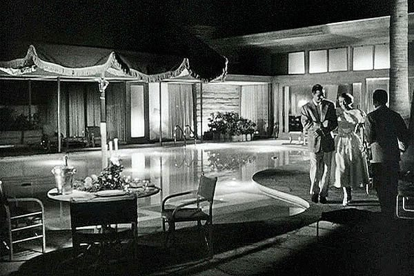 Joan Crawford and Richard Egan make their way around the pool at Frank Sinatra's Twin Palms Estates in Palm Springs.