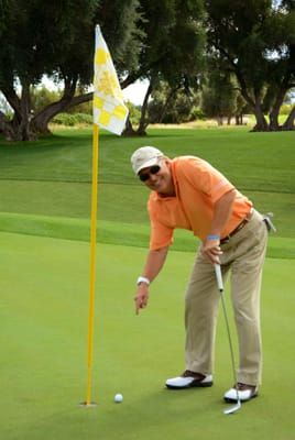 Kris Long, KPSP 2 News Anchor, makes a statement in his tangerine shirt by the Sunnylands yellow flag. Kris snagged second place in the Gross Division with a score of 41.