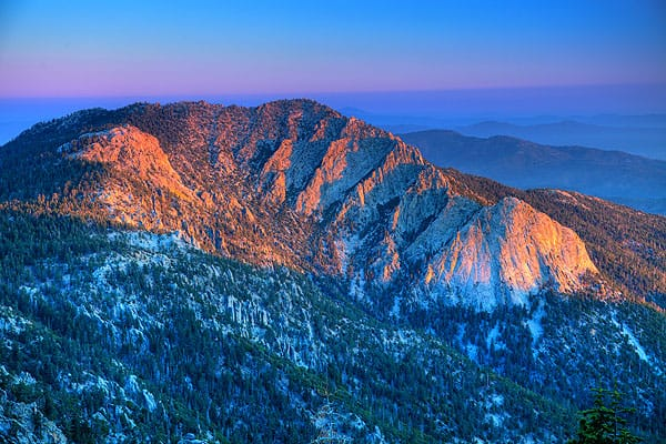 From Pacific Crest Trail, Saddle Junction in the shadowed foreground, Brewster watches the sun set over Tahquitz Peak and Lily Rock.