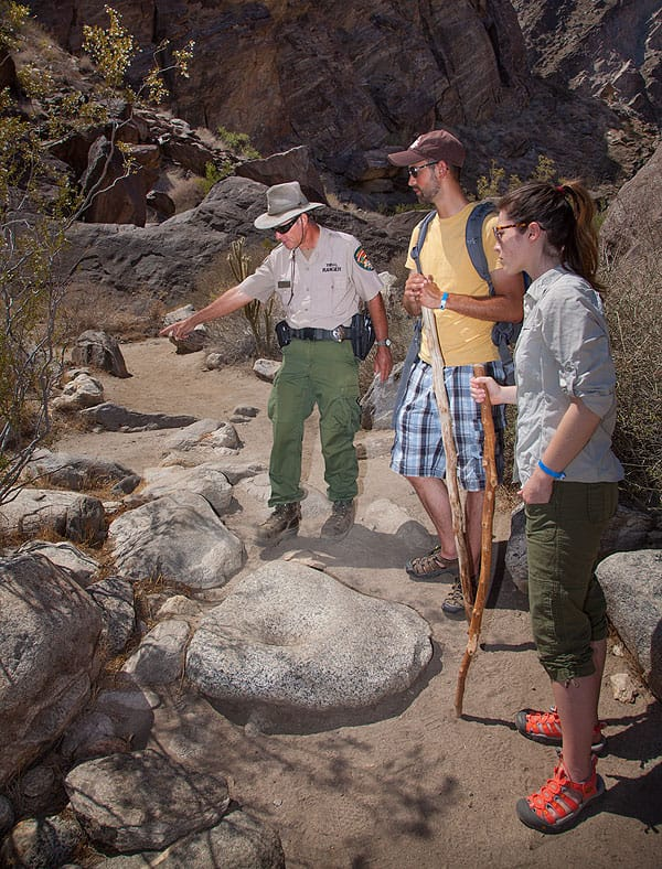 "Tahquitz Tribal Ranger ""Mountain Bob"" Hepburn guides hikers Jessie Conover and Cameron Brooks on the two-mile trail loop at Tahquitz Canyon, pointing out bedrock mortar artifacts left behind by the Cahuilla Indians."