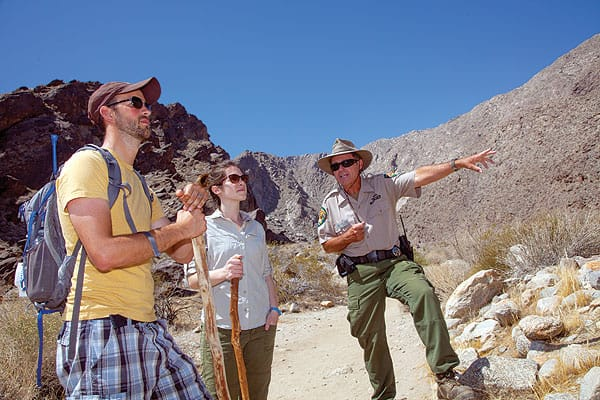 "Tahquitz Tribal Ranger Robert ""Mountain Bob"" Hepburn guides hikers Jessie Conover and Cameron Brooks on the two-mile loop trail, pointing out native plants used by the Cahuilla Indians, along the way."