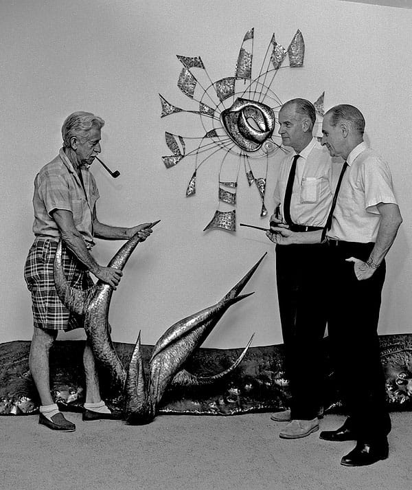 O.E.L. Graves, E. Stewart Williams, and unidentified man, examine a sculpture created for the interior. The sculpture hangs above the Pines Café.
