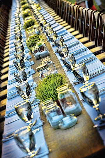 Hot tips for cool desert weddings - Low centerpieces with a casual look, such as these boxes of wheatgrass, are an unobtrusive, rustic touch. The site for this rehearsal dinner was the back palm tree lawn at Jackalope Ranch in Indio. Also, for multiple events, consider round tables for one and king's tables for another.