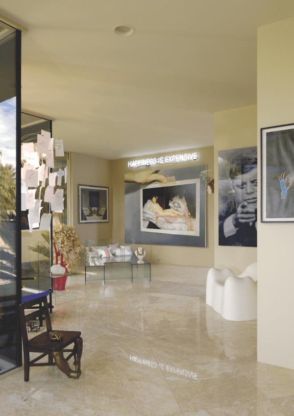 The master suite gallery hall includes the neon sign Happiness Is Expensive by Alejandro Diaz, Olympia's Scandal painting by Victor Rodriguez, glass chair and bed set by Vikky Alexander, Molar Chair by Wendell Castle, and Marilyn vs. JFK — JFK vs. Marilyn by Alex Guofeng Cao.