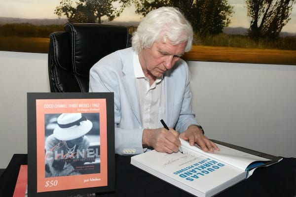 Douglas Kirkland signs copies of his book. 'Coco Chanel: Three Weeks -1962.'