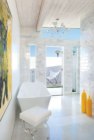 The hand-cut Carrara tiles continue in one master bath with a shapely freestanding tub and sputnik chandelier. Thanks to the reconfigured floor plan, the former front door opens into this tranquil retreat.