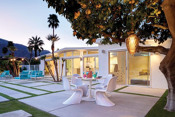 As the sun sets behind the mountain, the Alexander-style home and its outdoor lighting begin to glow, setting a chic stage for casual outdoor dining.