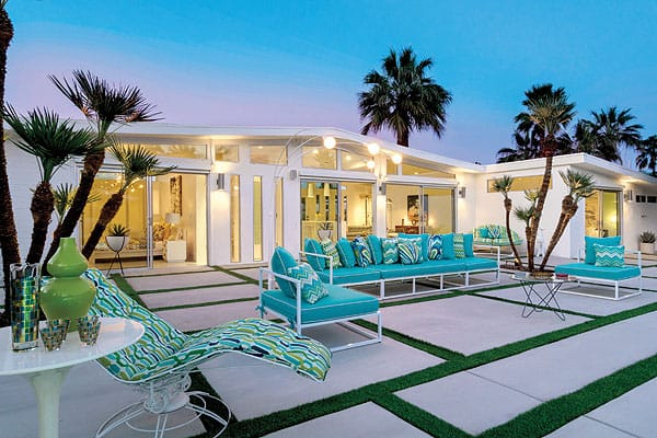 A patterned custom sun lounger by Hollywood Home pops in the outdoor living room that faces the pool.