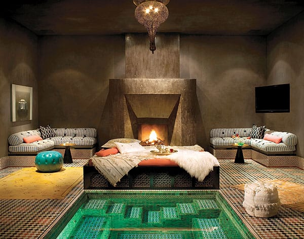 The sophisticated hammam, a classic Moroccan spa, radiates an almost sacred sense of serenity, featuring a step-down spa, organic spa bed, tadelakt plaster fireplace wall, dual sitting areas with massage tables hidden within, and an expansive steam room.