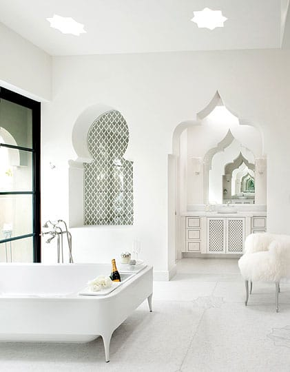 Ornate windows and doorways in the cloud-white master bath echo the sculpted arches along the home's exterior. A bottle of Champagne chills on ice in a niche along the oversized tub.