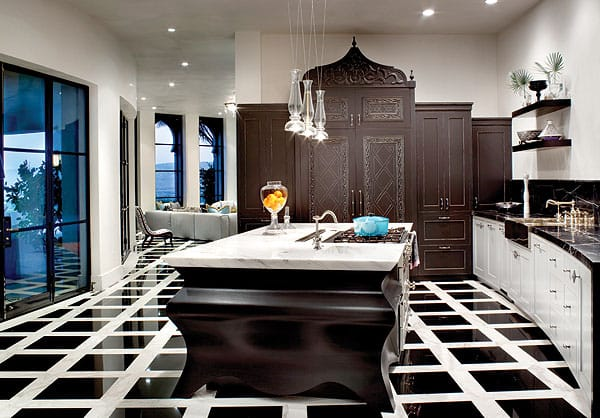 A striking black and white marble floor transitions seamlessly from the family room into the kitchen, where the focal point is a mahogany island topped in honed white marble.
