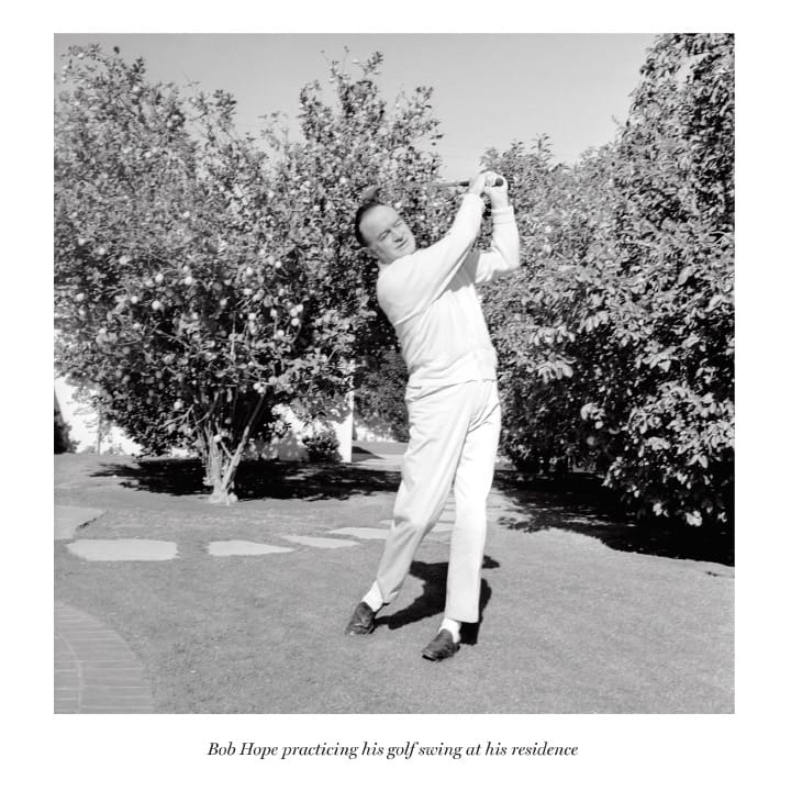 Bob Hope practicing his golf swing at his residence.